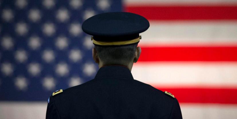 Un oficial del ejército de EEUU escucha a un orador con la bandera de...