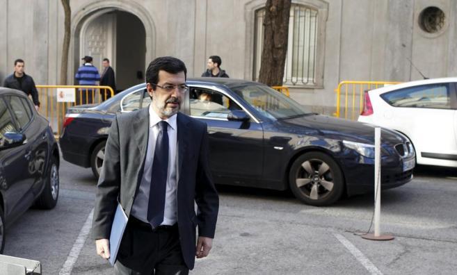Fernando Andreu camina delante de un coche negro y otro blanco y al...