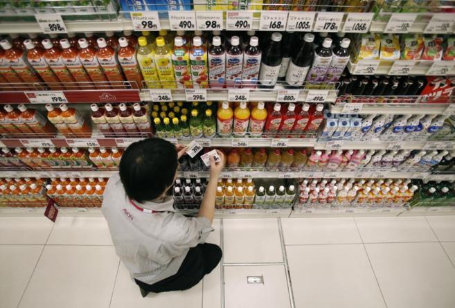 Un empleado coloca etiquetas de precios en un supermercado de Tokio.