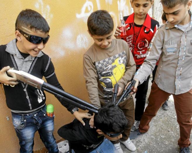 Niños sirios y palestinos juegan con armas de juguete en el campo de...
