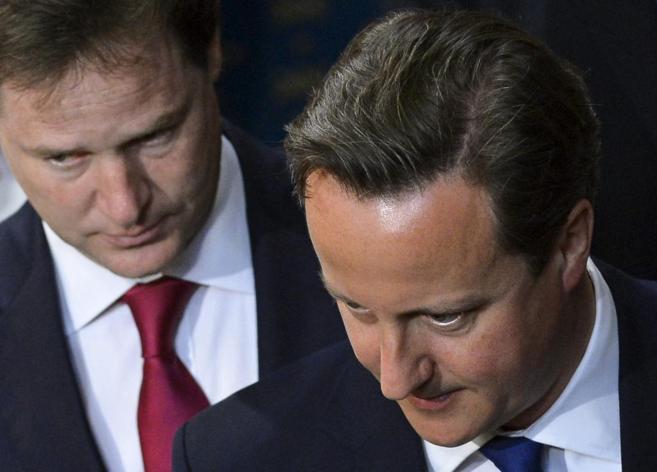 David Cameron (en primer plano) y Nick Clegg, en el Parlamento...