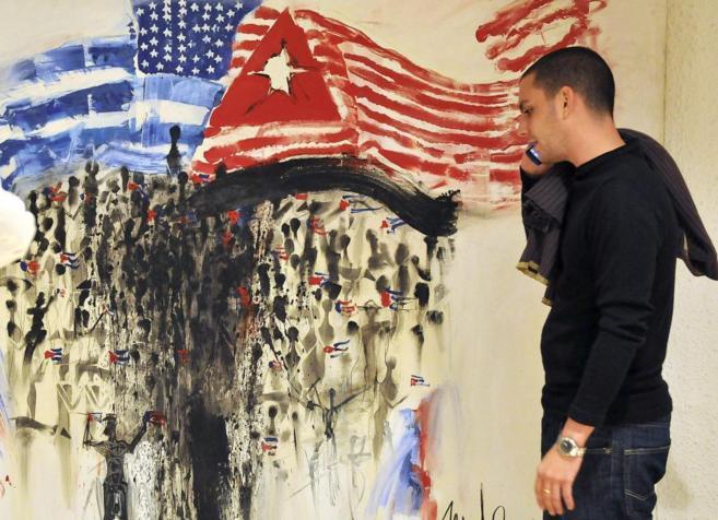 Un cubano habla con su móvil ante una pintada con banderas de EEUU y...