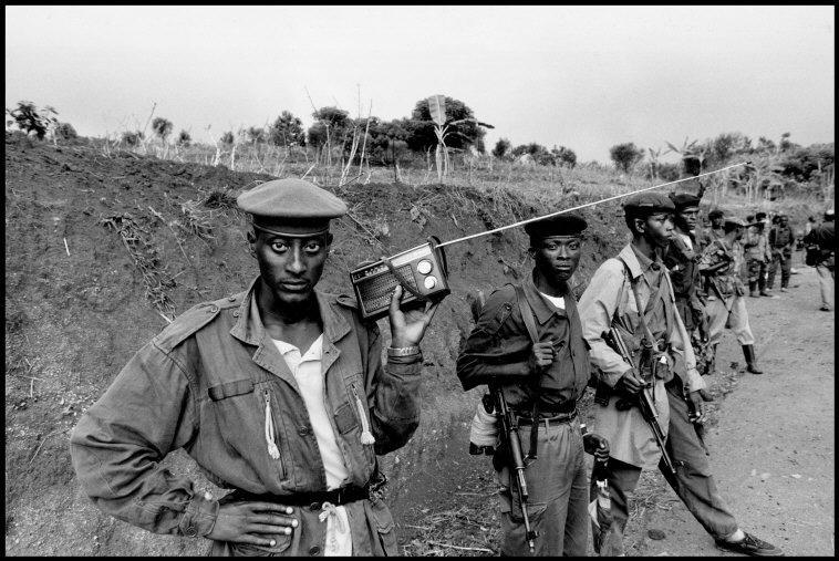 Rebeldes del Frente Patriótico Ruandés vigilan una carretera.