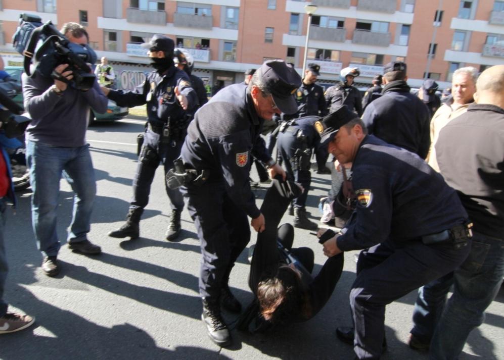 Policías retiran del suelo a un joven que participaba en la protesta...