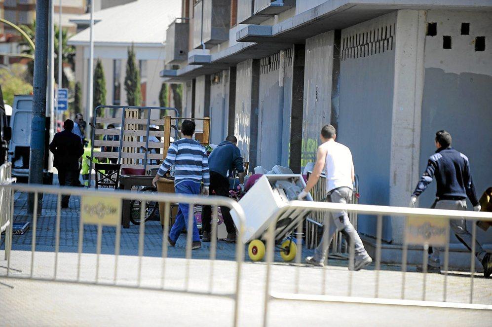 Los desalojados reúnen sus enseres en la calle.
