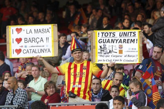 Un aficionado del Barça muestra dos cartulinas en el Camp Nou el...