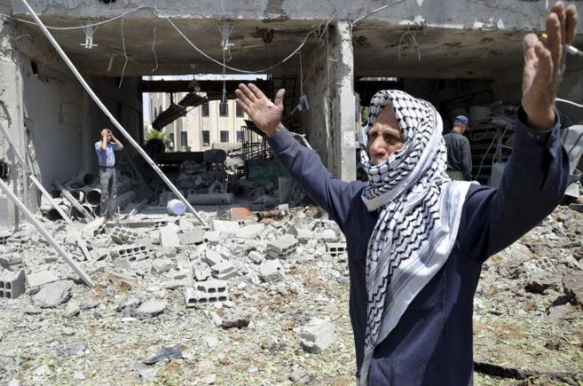 Un sirio se lamenta ante un edificio destruido en la localidad de...