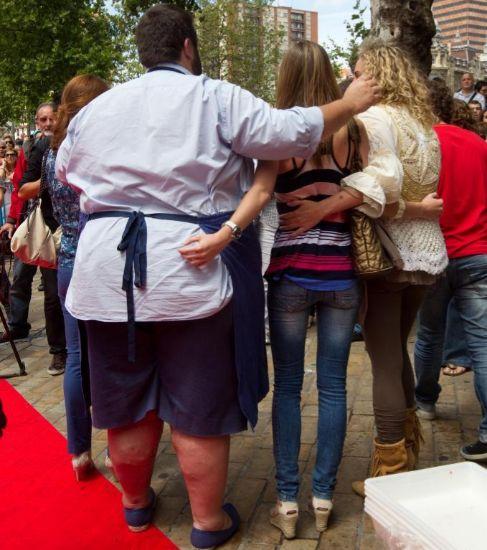 Un cocinero con sobrepeso posa de espaldas con una mujer delgada