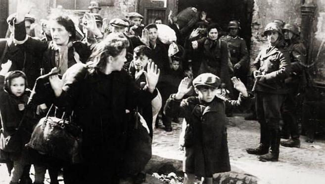 Varios judíos levantan la mano mientras un nazi les apunta con una...