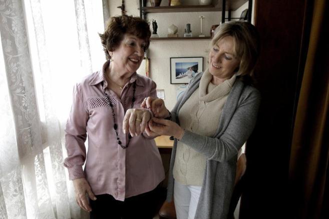 Una voluntaria atiende a una anciana que vive sola en Barcelona.