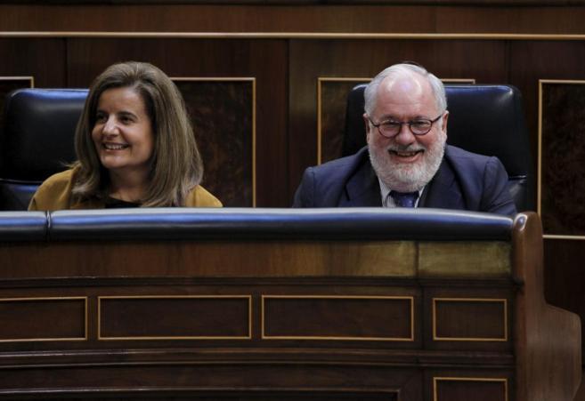 Miguel Arias Cañete, con la ministra Fátima Báñez, en el Congreso...