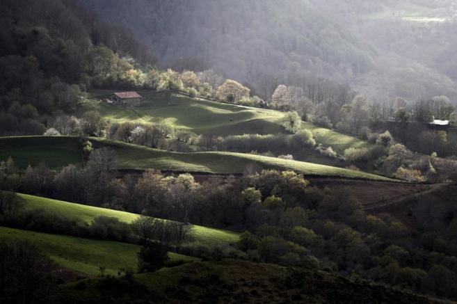 El sol asoma entre las nubes del pirineo navarro en el valle del...