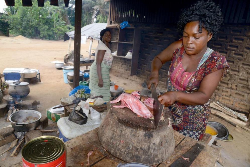 Una mujer cocina en un 'maquis', un pequeño restaurante en Liberia....