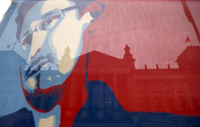 El rostro de Snowden, dibujado sobre una bandera ondeando en Berlín.