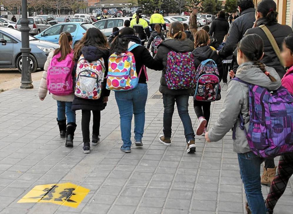 Un grupo de niñas camina hacia el colegio.