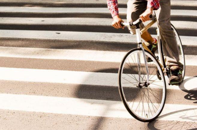 Una persona montando en bicicleta por la ciudad.