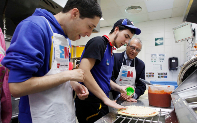 Jóvenes autistas preparando una pizza.