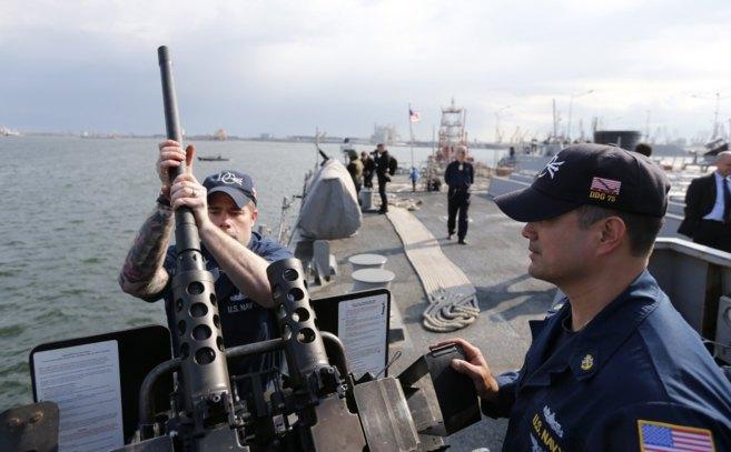 Miembros de la tripulación montan un arma en la cubierta del...