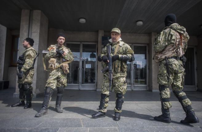 Hombres armados montan guardia ante un edificio de la administración...