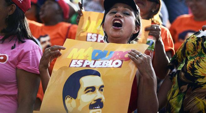 Una seguidora de Nicolás Maduro sostiene un cartel de apoyo al...