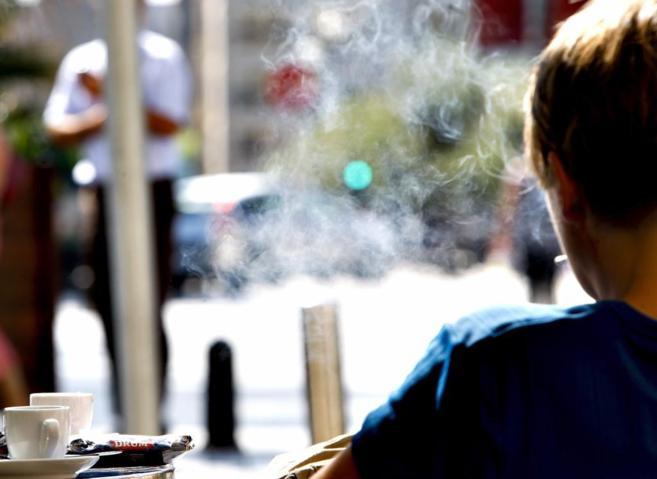 Una persona fuma mientras toma café en una terraza.