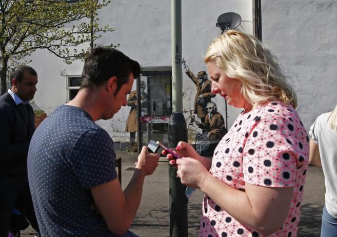 Dos personas miran sus móviles tras fotografiar una obra atribuida a...