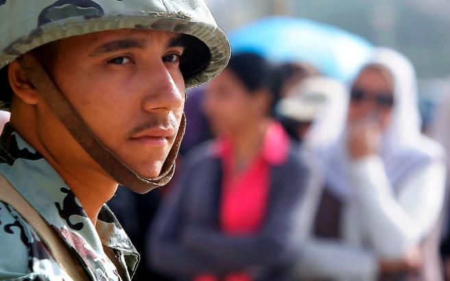 Un soldado egipcio observa  una cola de votantes en El Cairo.