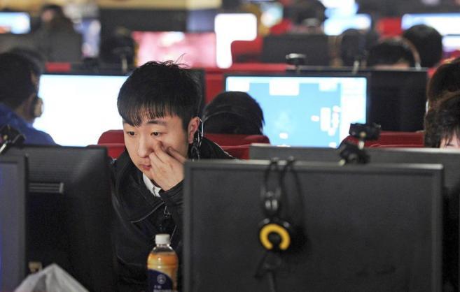 Un joven chino navega por internet en un locutorio de la ciudad de...