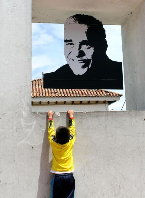 Un niño se cuelga frente a un retrato de Gabriel García Márquez, en...