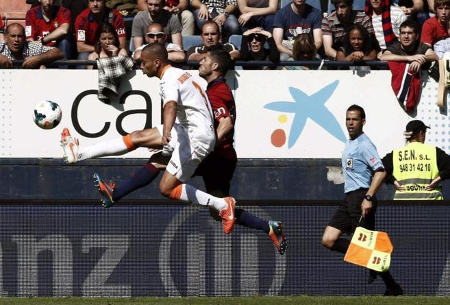 Cejudo intenta controlar el esférico ante el defensa del Valencia...
