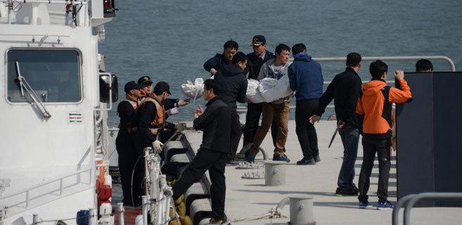 Los equipos de rescate surcoreanos transportan uno de los cuerpos sin...