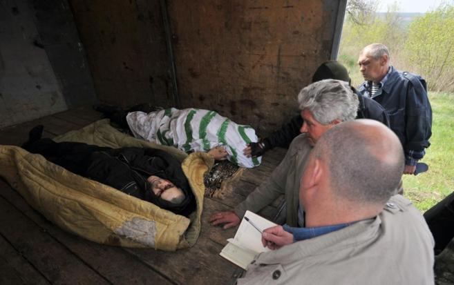 Policías ucranianos examinan los cuerpos de dos separatistas...