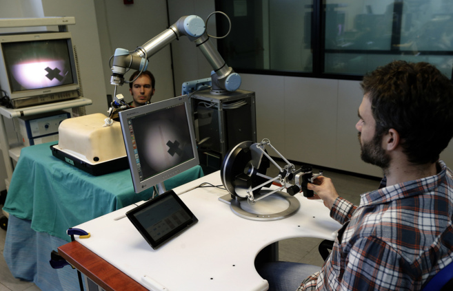 Ingenieros participantes en el proyecto manejan el prototipo del robot...