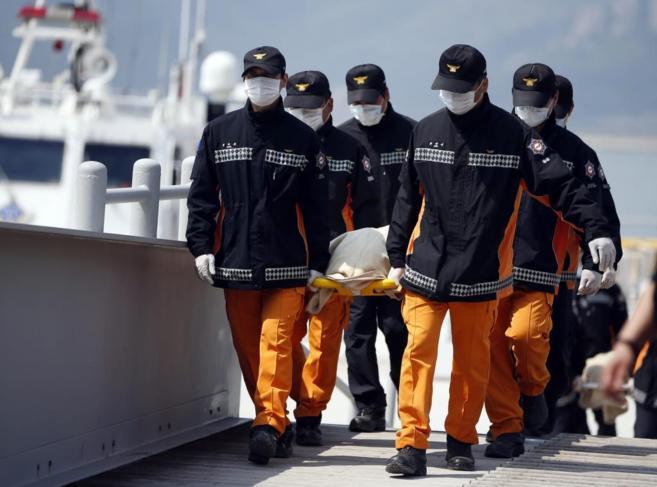 Varios operarios del servicio de rescate surcoreano transportan uno de...