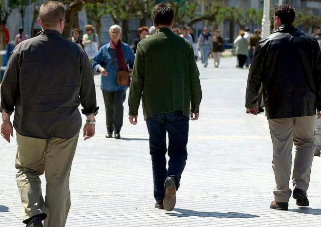 Escoltas, de espaldas, acompañan  a un político