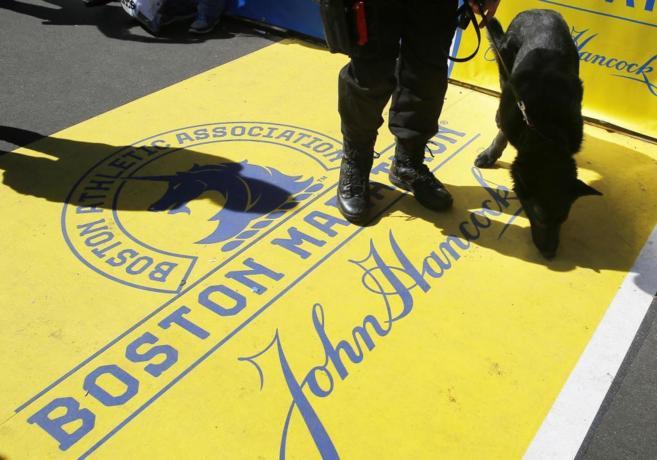 Un agente patrulla, junto con un perro policía, en la línea de meta...