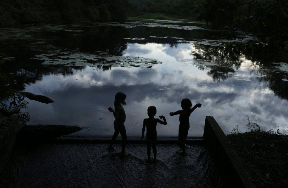 Los niños juegan en el borde de una laguna en la Reserva Ecológica...