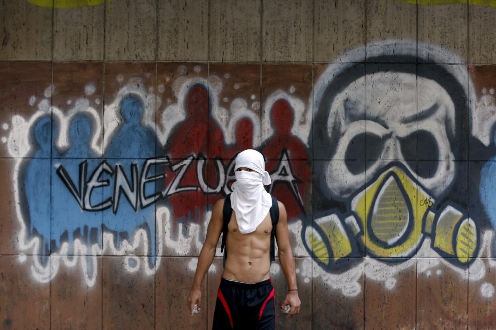 Un manifestante contra el gobierno  se encuentra cerca de un graffiti...