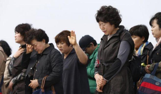 Un grupo de personas rezando por los pasajeros desaparecidos.