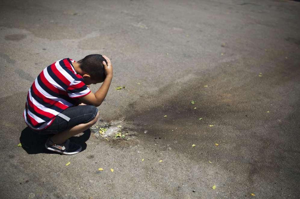 Un niño israelí mira metralla en un estacionamiento de la ciudad...