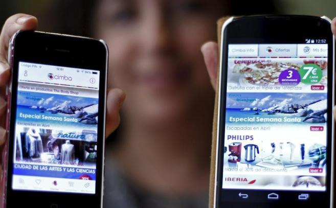 La directora general de Cimba, Juana Lara, muestra dos móviles con la...