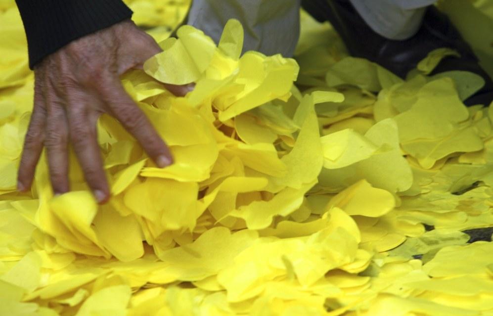 Un hombre recoge pétalos d epapel amarillos del suelo al salir de la...