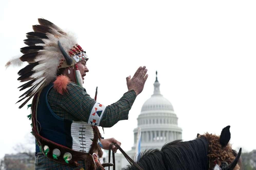 Un nativo americano se sienta en su caballo en frente del Capitolio de...