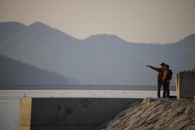 Dos miembros del equipo de rescate señalan el lugar donde se hundió...