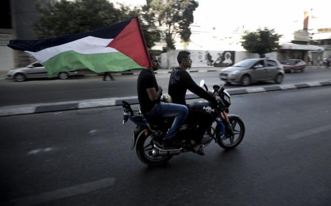 Palestinos ondean una bandera nacional por las calles de Gaza para...