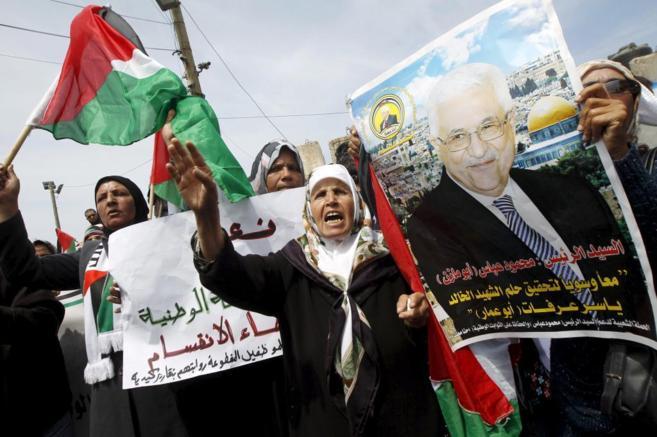 Palestinos corean eslóganes y alzan pancartas a favor del presidente,...