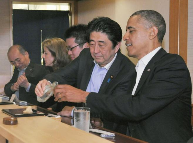 El primer ministro japonés, Shizo Abe llena el vaso del presidente...