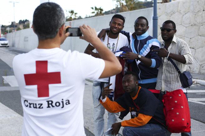 Un miembro de Cruz Roja fotografía a un grupo de inmigrantes. CARLOS...