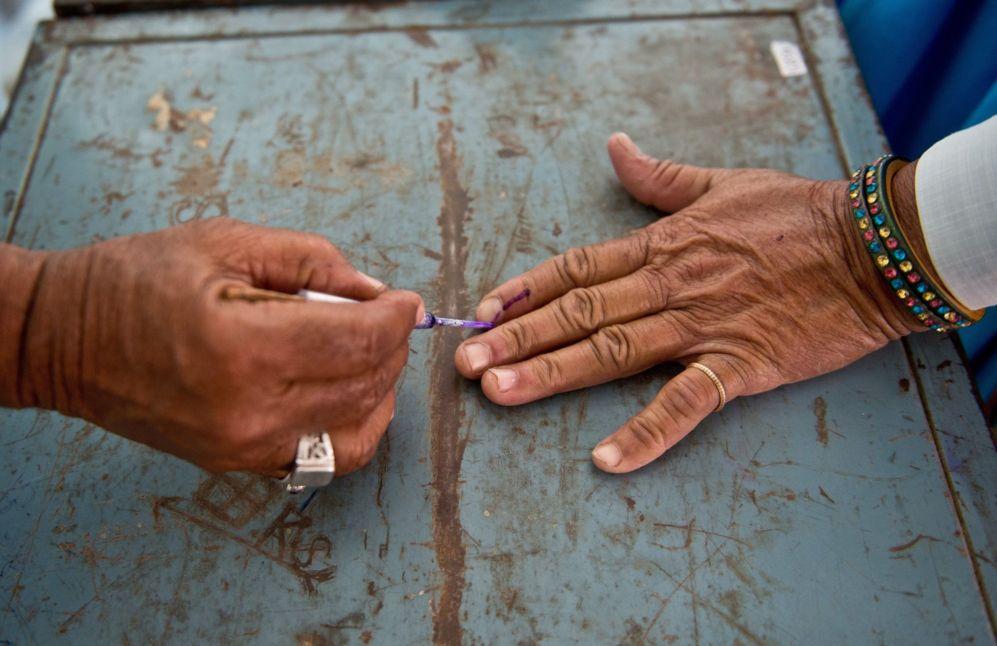 Escrutador indio marca el dedo de un votante en una cabina de...
