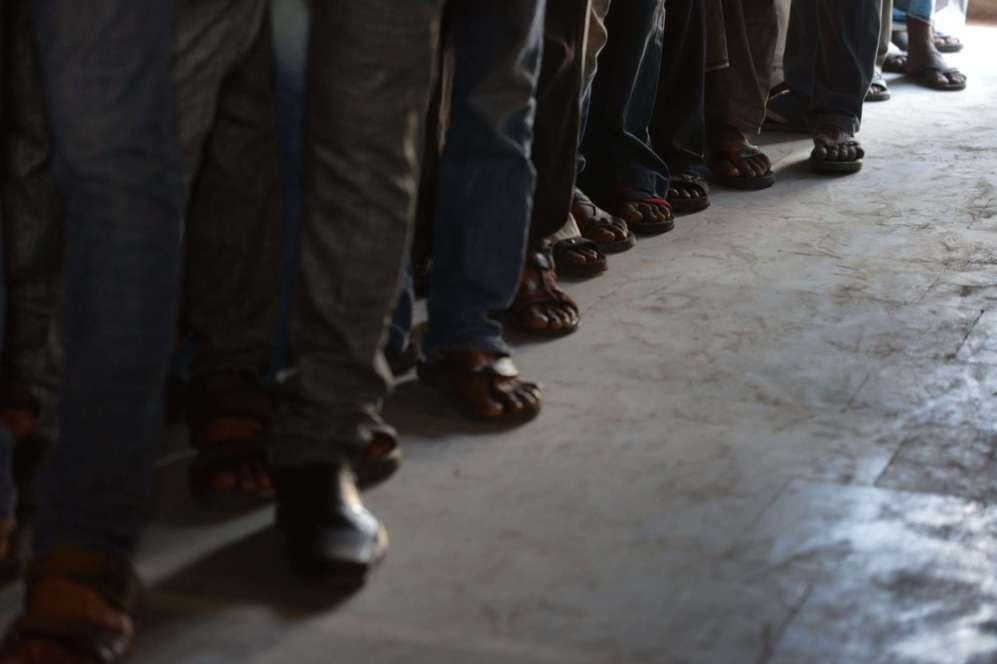 Hombres indios hacen fila para emitir su voto en un colegio electoral...
